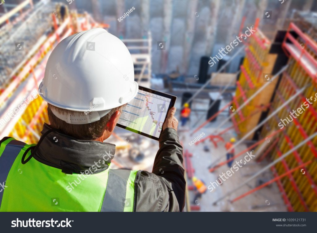 stock-photo-civil-engineer-or-architect-with-hardhat-on-construction-site-checking-schedule-on-tablet-computer-1039121731