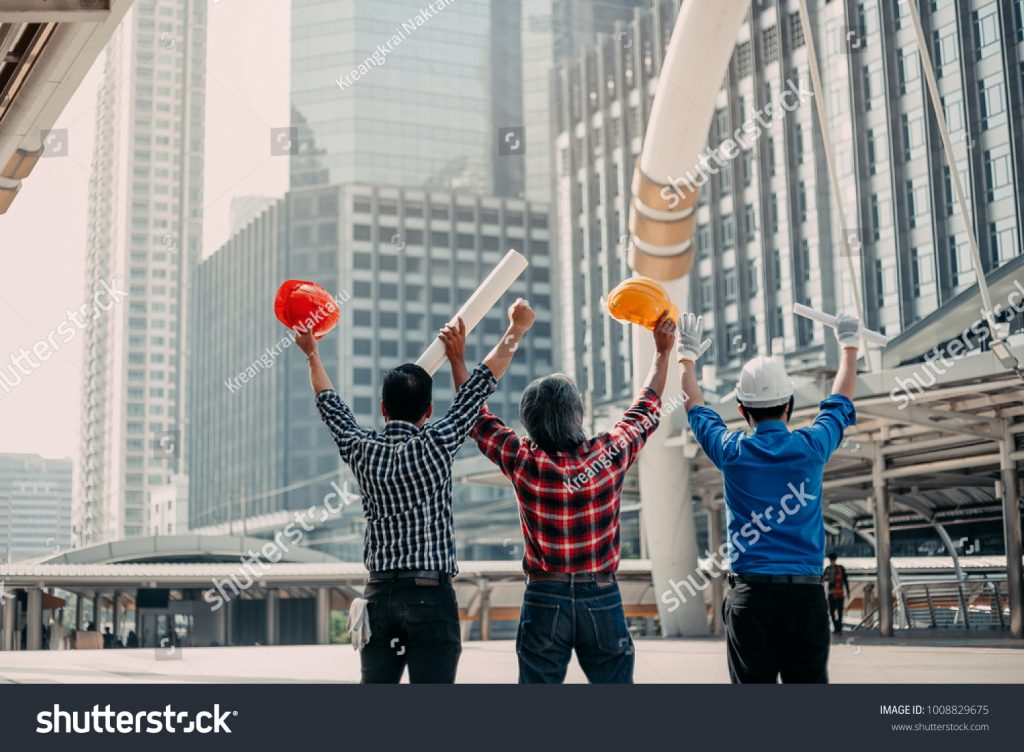 stock-photo-team-engineering-happy-smile-foreman-look-at-complete-site-project-plan-lift-hands-to-celebrate-1008829675